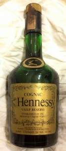 Cognac is printed above Hennessy; with the 'bras armé' on the shoulder blob; Arabic characters below on the label.