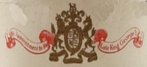 By appointment to the Late King George V on a banner and with their coat of arms
